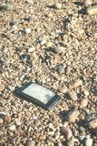 Broken mobile phone on a stony beach. Broken mobile phone with cracked screen on a stony beach, selective focus, color toned picture stock images