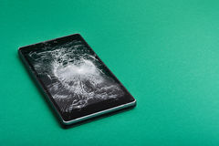 Broken mobile phone on green stock images