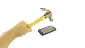 Broken mobile phone. Hand holding hammer and smartphone with a broken screen over the white background royalty free stock image