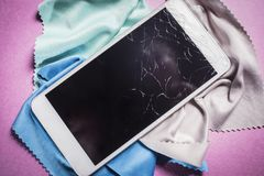 Broken mobile phone lies on a multicolored background.  royalty free stock photo