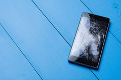 Broken mobile phone on painted wooden table. Background royalty free stock image