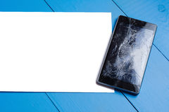 Broken mobile phone with paper sheet on wooden table. Broken mobile phone with paper sheet on painted wooden table royalty free stock photography