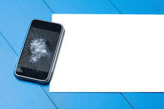 Broken mobile phone with paper sheet on wooden table. Broken mobile phone with paper sheet on painted wooden table royalty free stock photo