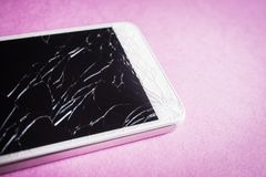 Broken mobile phone on a pink background.  royalty free stock photo