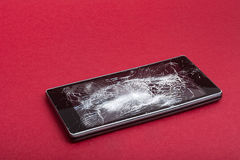 Broken mobile phone on red. Background stock photos