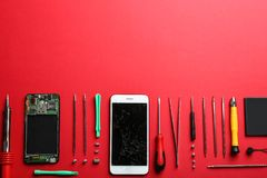 Broken mobile phone and repair tools on color background, flat lay royalty free stock images