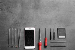 Broken mobile phone and repair tools on table, flat lay. Space for text stock photography