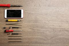 Broken mobile phone and repair tools on wooden table, flat lay. Space for text stock images