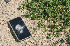 Broken mobile phone on sand concept. Background royalty free stock image