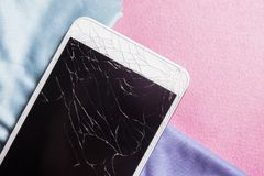 Broken mobile phone screen. On a pink background royalty free stock photos