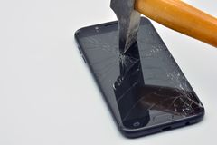 Broken mobile phone screen with a hammer. LCD screen of a broken, cracked and unusable mobile phone, with a hammer royalty free stock photography