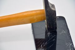 Broken mobile phone screen with a hammer royalty free stock images