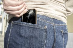 Broken mobile phone up from her pocket jeans pant after sitting. Woman pulls a broken mobile phone up from her pocket jeans pant after sitting over it royalty free stock images