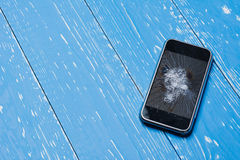 Broken mobile phone on vintage painted table close up. Broken mobile phone on vintage painted wooden table royalty free stock photo