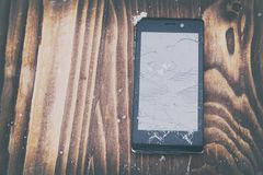 . broken mobile phone on a wooden background. Mobile phone repair. there is toning. Broken mobile phone on a wooden background. Mobile phone repair. there is royalty free stock images