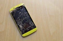 Broken mobile phone on wooden background stock image
