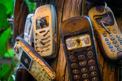 Broken mobile phones. Old mobile phones are nailed to a trunk. The severely damaged mobile phones transfer the message that phones are to be turned off here Stock Image