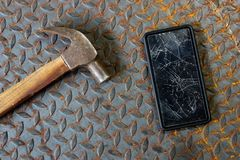 Broken mobile screen and hammer on old metal diamond plate or old checkered steel plate. Broken mobile screen and hammer on old metal diamond plate or old royalty free stock images
