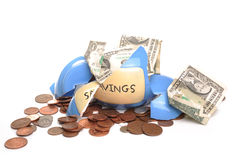 Broken money box. Photograph of a broken money box and loose change and american dollars Royalty Free Stock Image