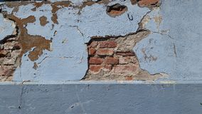 Broken mortar on brick wall. Broken light blue mortar over a red brick wall Royalty Free Stock Photo