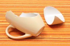 Broken mug, shattered cup on orange cloth Royalty Free Stock Photo