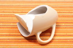 Broken mug, shattered cup on orange cloth Royalty Free Stock Photography