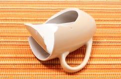 Broken mug, shattered cup on orange cloth Royalty Free Stock Photography