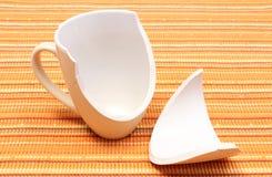 Broken mug, shattered cup on orange cloth Stock Photography