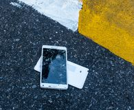Broken New Smartphone on asphalt road. Someone dropped device. Cracks on a big display Royalty Free Stock Photography