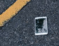 Broken New Smartphone on asphalt road. Someone dropped device. Cracks on a big display Stock Image