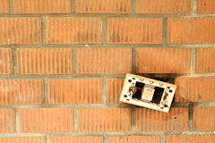 A broken on/off switch on orange brick wall. This photo is took on National Taiwan University. A broken switch on orange brick wall. The texture of bricks is Stock Photos