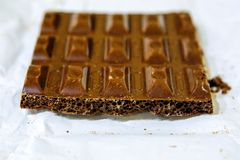Broken off tile of Russian milk porous chocolate, close-up royalty free stock photo
