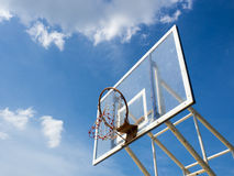 Broken old basketball hoop against blue sky. Broken old basketball hoop with backboard against  blue sky, white cloud Royalty Free Stock Images