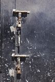 Old scratched black steel door with two large rusty latches and padlocks hanging from them. Broken and old black iron door with many damages and two big rusty stock photo