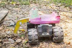 Broken old excavator toy on ground and dry leaves. Royalty Free Stock Photo