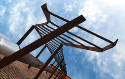 Broken old fire escape metal stairs. Above blue cloudy sky Stock Photo