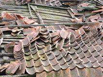 Broken old home roof in village, Lithuania. Red tile on broken old home roof in village stock photo