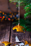 Broken old vintage Christmas ball and christmas tree. Broken old vintage Christmas ball on wooden table. Christmas lights and Christmas tree royalty free stock images