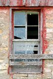 Broken Old Window on Abandoned Barn Background. The glass is broken on an old window framed with weathered barnwood on a vintage barn Stock Images