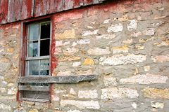 Broken Old Window on Abandoned Barn Background. The glass is broken on an old window framed with weathered barnwood on a vintage barn Royalty Free Stock Image