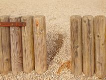 Broken old wooden palisade, old wooden stockade, fence. Stony background Royalty Free Stock Photo