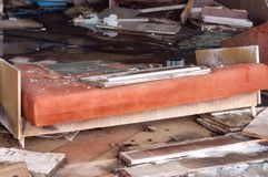 Broken orange couch and other furniture in destroyed shop in Pripyt stock photos