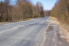 Broken out-of-town asphalt road Stock Images
