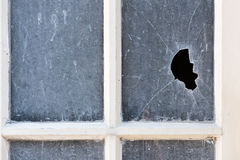 Broken pane of glass in an old window. Broken shattered pane of glass with a gaping hole through it in an old opaque window with wooden frame Royalty Free Stock Images