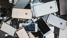Broken panels and screens of iPhone. TOMSK, RUSSIA - November 29, 2017: broken panels and screens of iPhone phones lie in the service and are preparing for royalty free stock photography