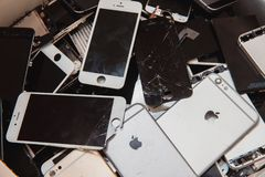 Broken panels and screens of iPhone. TOMSK, RUSSIA - November 29, 2017: broken panels and screens of iPhone phones lie in the service and are preparing for stock photography