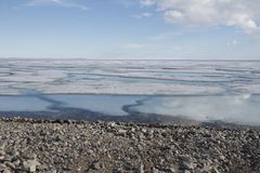 Broken pans of sea ice on ocean coast with blue sky and pebble beach along the Northwest Passage Stock Photo
