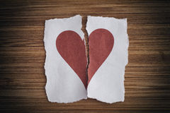 Broken paper heart. On a wooden background. Light noise effect added. Vignette Royalty Free Stock Image