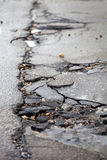 Broken pavement and pothole asphalt road after winter. Stock Photo