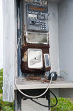 Broken pay phone handset and coin return Stock Image